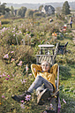 Young woman relaxing in cottage garden - KNSF00778