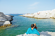 Greece, Milos, Man lying rocks at the White Beach of Sarakiniko - GEM01305