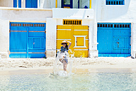 Greece, Milos, Firopotamos Beach, Womsn running into sea, splashing water - GEMF01332