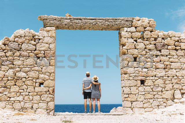 Greece, Milos, Firopotamos Beach, Couple standing in door in stone wall, looking at distance - GEMF01335