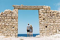 Greece, Milos, Firopotamos Beach, Couple standing in door in stone wall, looking at distance - GEMF01335
