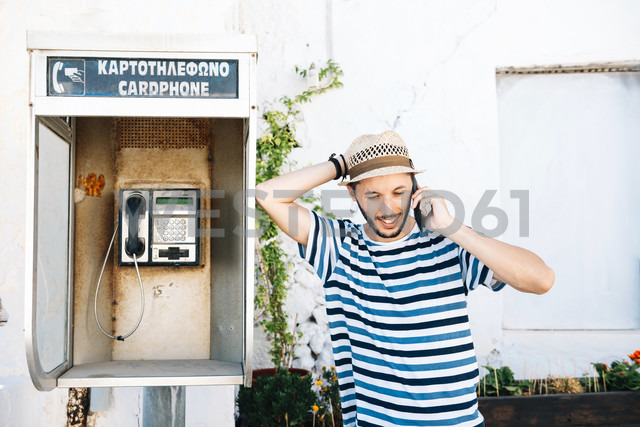 Greece, Milos, Klima, Man talking on cell phone, leaning against old telephone booth - GEMF01338