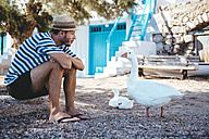 Greece, Milos, Klima, Man sitting on ground looking at geese - GEMF01341