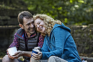 Happy couple sitting outdoors with coffee mugs - FMKF03317