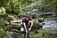 Man washing dishes at a river - FMKF03320