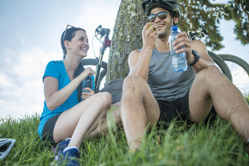 Young couple mountain biking in nature, taking a break under tree - ZEF11871
