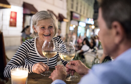 Senior couple drinking wine at an outdoor bar - HAPF01256