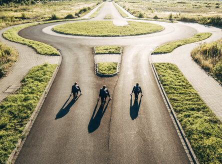 Three businessmen starting race at roundabout - KNSF00795