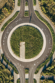 Businessman in roundabout with scattered papers - KNSF00798