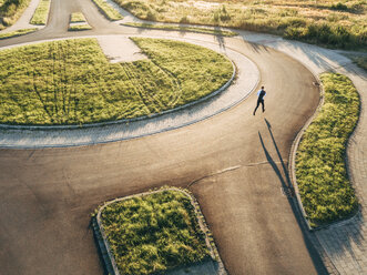 Businessman running in roundabout - KNSF00807