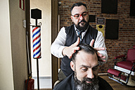 Barber checking the haircut of a man - ABZF01678