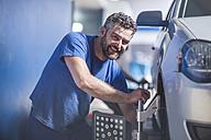 Smiling car mechanic in a workshop - ZEF11988