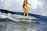 Indonesia, Bali, legs of woman on surfboard - KNTF00589