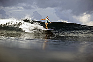 Indonesia, Bali, woman surfing - KNTF00595