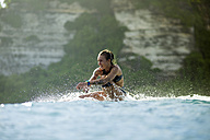 Indonesia, Bali, woman sitting on surfboard in the sea - KNTF00604