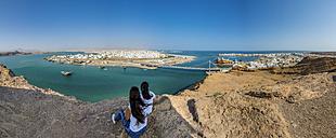 Oman, Ash Sharqiyah, Ad Daffah, back view of two women looking at seaport Sur and Blue Lagoon - AMF05161