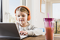 Little girl sitting at home using laptop and headphones - UUF09530