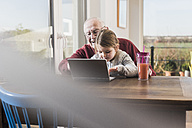 Grandfather and granddaughter using laptop together - UUF09536