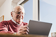 Senior man sitting at home, using laptop - UUF09545