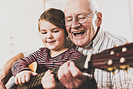 Grandfather and granddaughter playing together guitar - UUF09554