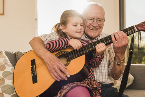 Grandfather and granddaughter playing together guitar - UUF09557