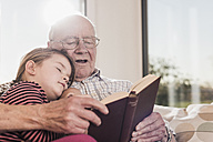 Grandfather reading out story for his granddaughter - UUF09572