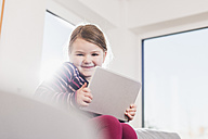 Little girl using digital tablet, sitting on couch - UUF09578