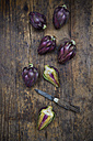 Sliced and whole purple organic artichokes and a pocket knife on dark wood - LVF05742