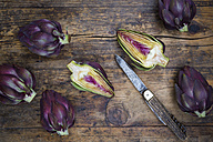 Sliced and whole purple organic artichokes and a pocket knife on dark wood - LVF05745