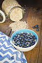 Bowl of overnight oats with blueberries on wood - LVF05753