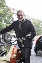 Smiling mature man with motor scooter - RBF05349