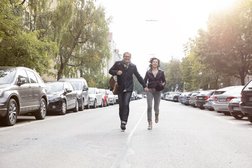 Mature couple running on street - RBF05358