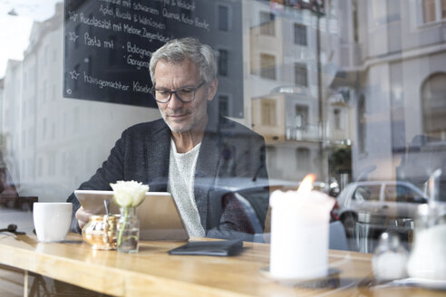 Mature man with tablet in a cafe - RBF05361