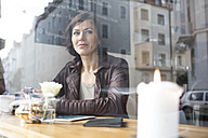 Woman in a cafe looking out of window - RBF05364