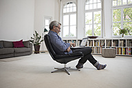 Mature man at home sitting in chair using laptop - RBF05373