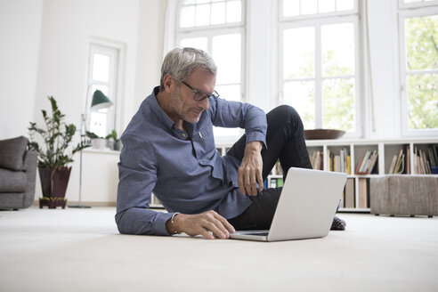 Mature man at home lying on floor using laptop - RBF05376