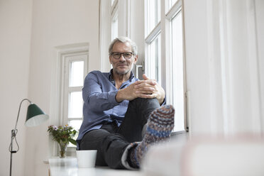 Relaxed mature man at home sitting at the window - RBF05379