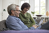 Smiling mature couple at home on the sofa sharing tablet - RBF05385