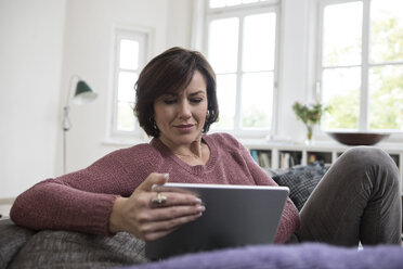 Woman at home sitting on the sofa using tablet - RBF05394