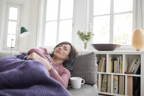 Woman with stomach ache lying on the sofa - RBF05397