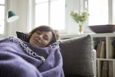 Woman with blanket lying on the sofa - RBF05400