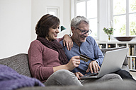 Smiling mature couple at home on the sofa shopping online - RBF05406
