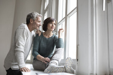 Mature couple looking out of window - RBF05418