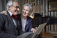 Happy senior couple using laptop at home - RHF01684