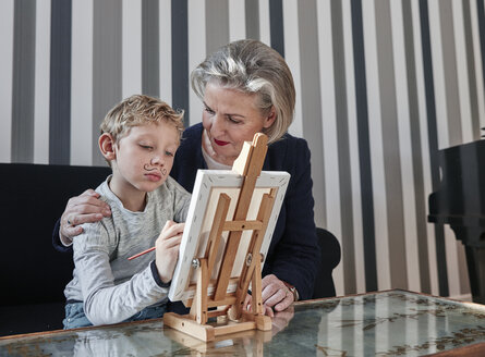 Grandmother and grandson with Dali moustache at easel - RHF01690