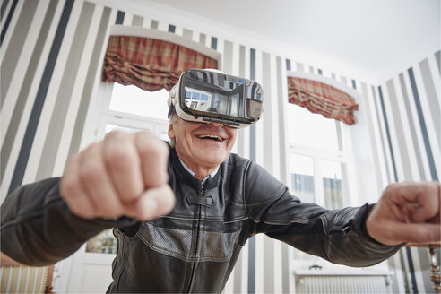 Senior man in motorcycle suit wearing VR glasses - RHF01696