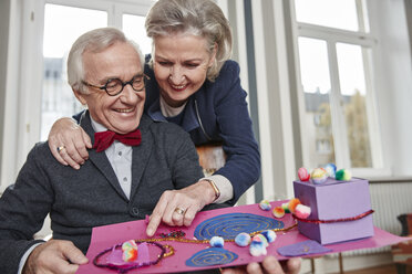 Happy senior couple looking at child's handicraft - RHF01705