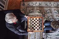 Grandfather and grandson playing chess in living room - RHF01717