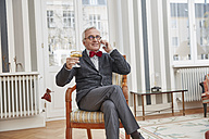 Smiling senior man on the phone sitting on chair with champagne glass - RHF01723