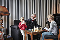 Grandfather and grandson playing chess in living room with girl sitting next to them - RHF01726